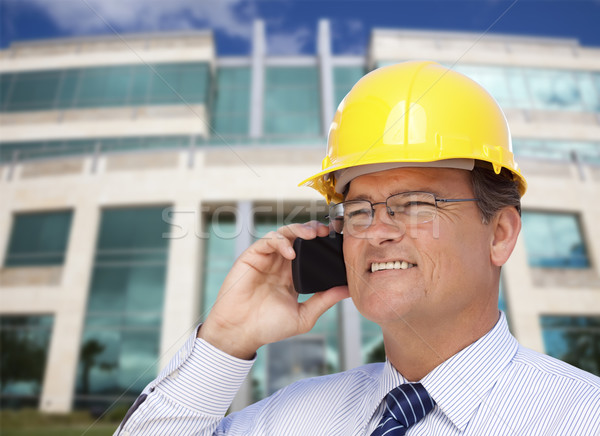 Contractor in Hardhat Talks on Phone In Front of Building Stock photo © feverpitch