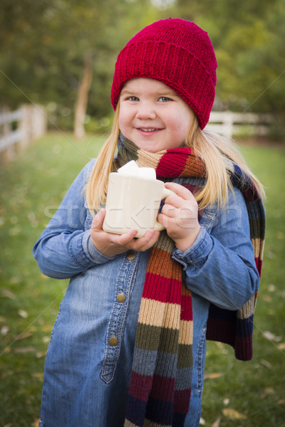 Cute Young Girl Holding Cocoa Mug with Marsh Mallows Outside Stock photo © feverpitch