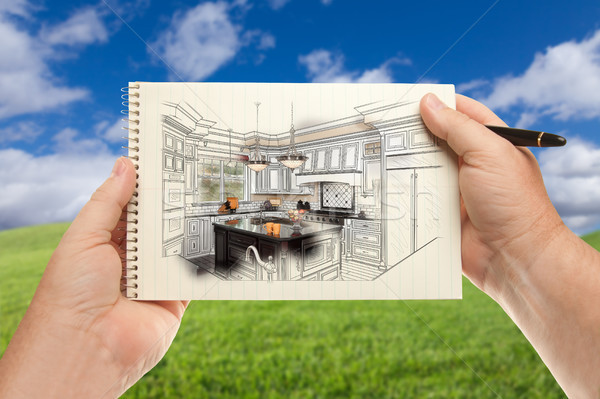 Male Hands Holding Pen and Pad of Paper Up with Custom Kitchen I Stock photo © feverpitch