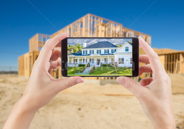 Female Hands Holding Smart Phone Displaying Photo of House with  Stock photo © feverpitch