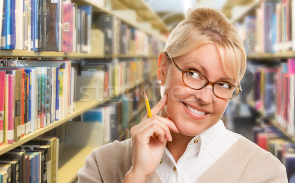 Beautiful Expressive Student or Teacher with Pencil in Library. Stock photo © feverpitch