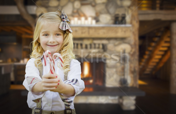 Cute Young Girl Holding Candy Canes in Rustic Cabin Stock photo © feverpitch