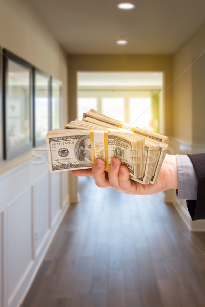 Male Hand With Stack of Cash Inside Hallway of House Stock photo © feverpitch