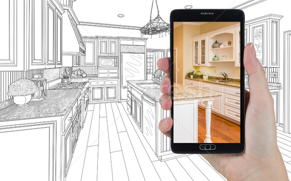 Hand Holding Smart Phone Displaying Photo of Kitchen Drawing Beh Stock photo © feverpitch