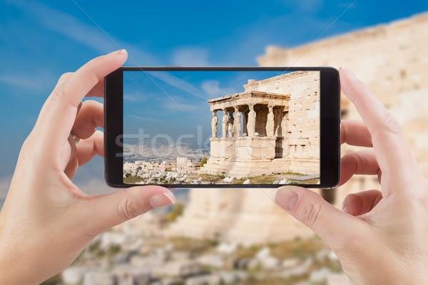 Female Hands Holding Smart Phone Displaying Photo of Caryatids i Stock photo © feverpitch