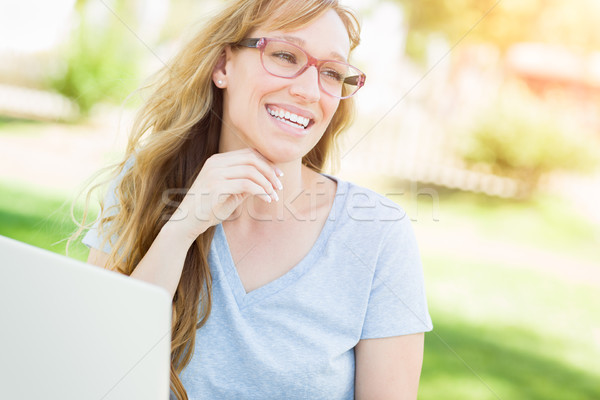 Young Adult Woman Wearing Glasses Outdoors Using Her Laptop. Stock photo © feverpitch
