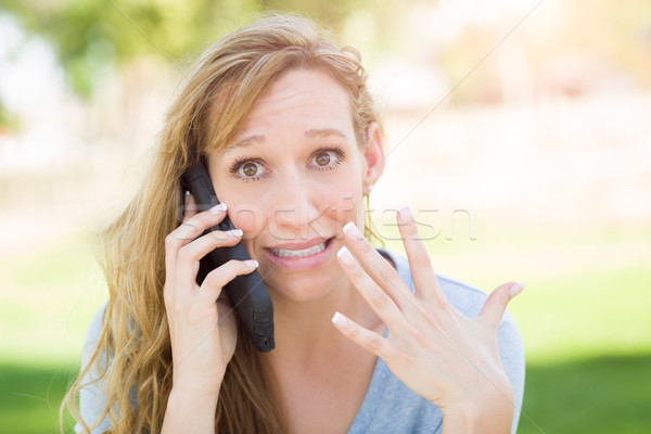 Stunned Young Woman Outdoors Talking on Her Smart Phone. Stock photo © feverpitch