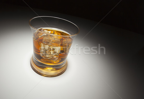 Glass of Whiskey and Ice Under Spot Light Stock photo © feverpitch