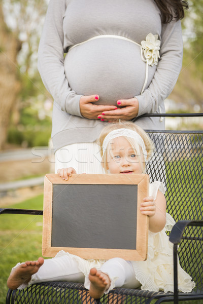 Pregnant Mom Behind Baby Girl in Chair Holding Blank Blackboard Stock photo © feverpitch