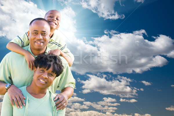 Happy African American Family Over Blue Sky and Clouds Stock photo © feverpitch