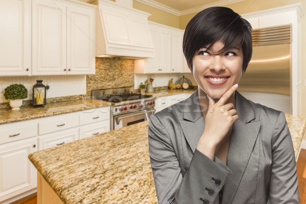 Mixed Race Woman Looking Back Over Shoulder Inside Custom Kitche Stock photo © feverpitch