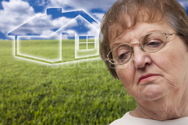 Stock photo: Melancholy Senior Woman with Grass Field and Ghosted House Behin