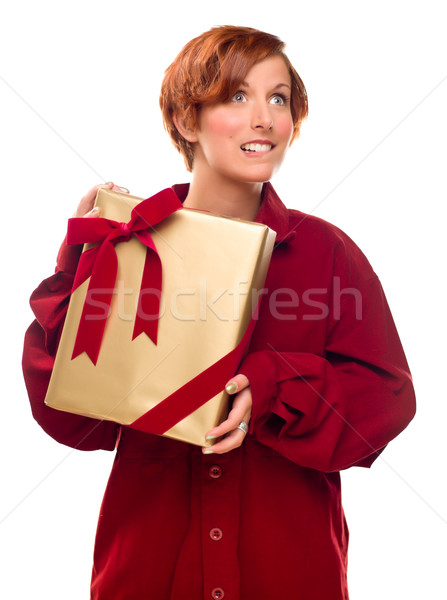 Pretty Red Haired Girl Biting Lip Holding Wrapped Gift Stock photo © feverpitch