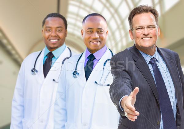 Halfbloed artsen achter zakenman hand te schudden twee Stockfoto © feverpitch