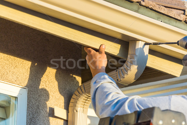 Worker Attaching Aluminum Rain Gutter and Down Spout to Fascia o Stock photo © feverpitch