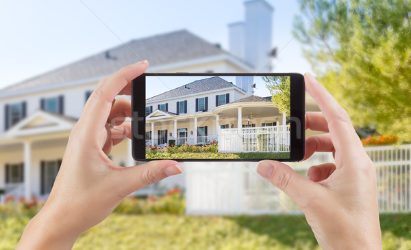 Female Hands Holding Smart Phone Displaying Photo of House Behin Stock photo © feverpitch