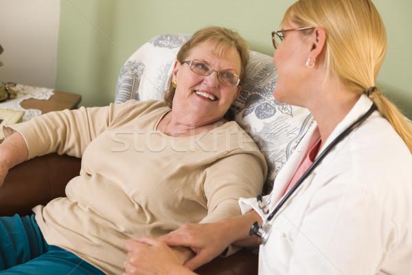 Doctor or Nurse Talking to Sitting Senior Woman Stock photo © feverpitch
