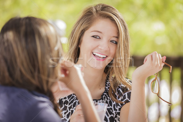 Stock photo: Attractive Mixed Race Girlfriends Talking Over Drinks Outside