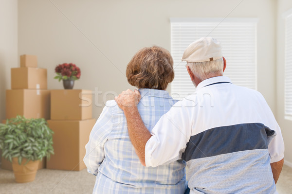 Senior Couple Facing Empty Room with Packed Moving Boxes and Pot Stock photo © feverpitch
