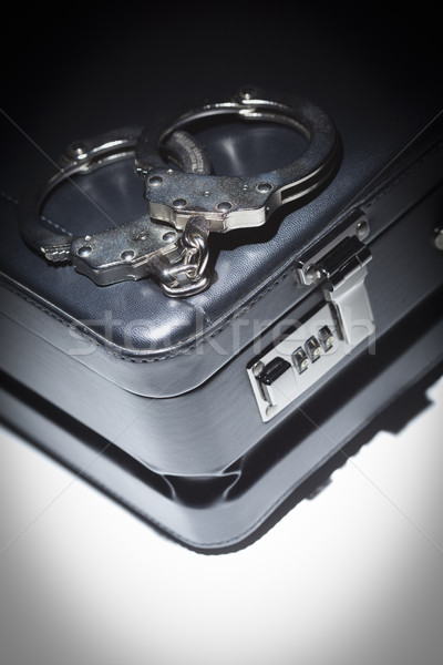 Pair of Handcuffs and Briefcase Under Spot Light Stock photo © feverpitch