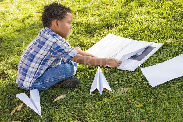Mixed Race Boy Learning How to Fold Paper Airplanes Stock photo © feverpitch