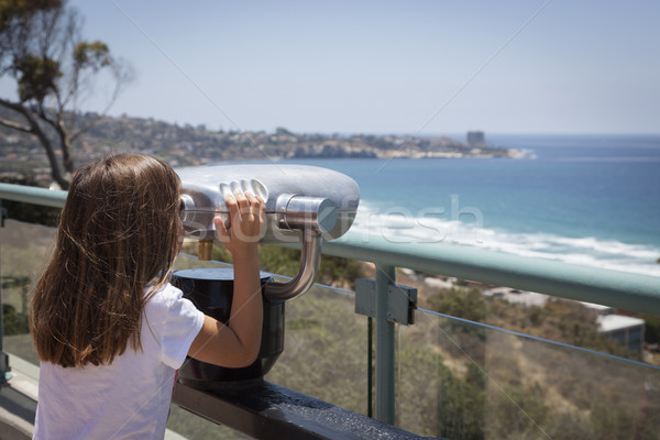 Young Girl Looking Out Over the Pacific Ocean with Telescope Stock photo © feverpitch