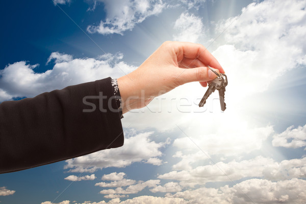 Female Holding Out Pair of Keys Over Clouds and Sky Stock photo © feverpitch