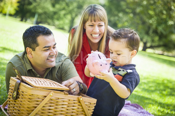 Mixed Race Couple Give Their Son a Piggy Bank at the Park Stock photo © feverpitch