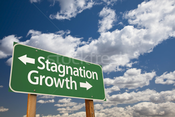 Stagnation or Growth Green Road Sign Over Clouds and Sky Stock photo © feverpitch