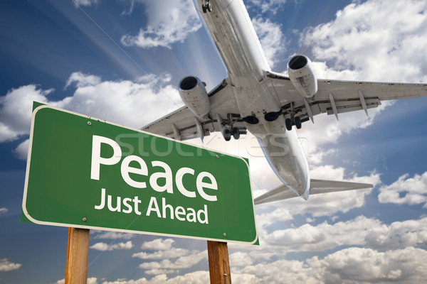 Peace Green Road Sign and Airplane Above Stock photo © feverpitch