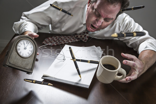 Stressed Man At Desk, Pens, Coffee, Glasses, Clock Flying Up Stock photo © feverpitch