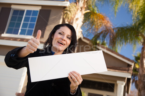 Attractive Hispanic Woman Holding Blank Sign in Front of House Stock photo © feverpitch