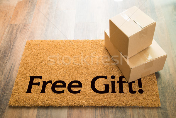 Free Gift Welcome Mat On Wood Floor With Shipment of Boxes Stock photo © feverpitch