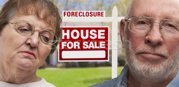 Stock photo: Depressed Senior Couple in Front of Foreclosure Sign and House