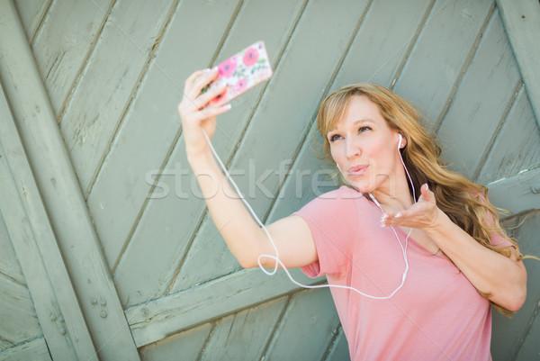 Fiatal felnőtt nő visel fülhallgató elvesz okostelefon Stock fotó © feverpitch