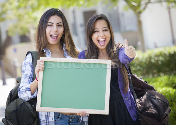 Mixed Race Female Students with Thumbs Up Holding Blank Chalkboa Stock photo © feverpitch