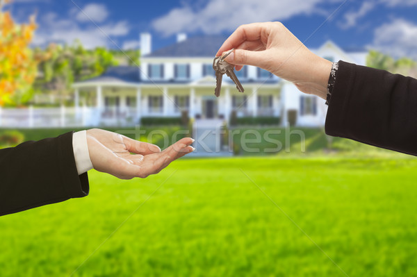 Agent Handing Over House Keys in Front of New Home Stock photo © feverpitch