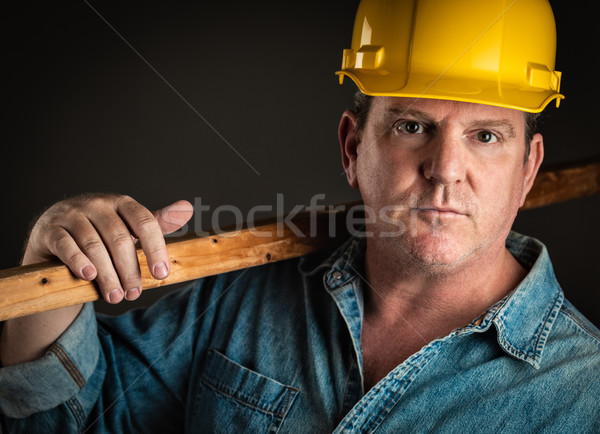 Serious Contractor in Hard Hat Holding Plank of Wood With Dramat Stock photo © feverpitch