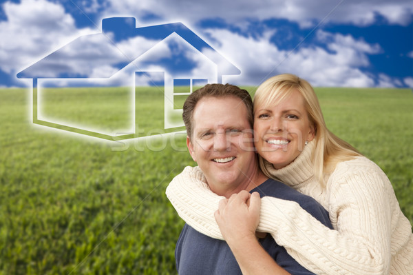 Happy Couple Hugging in Grass Field with Ghosted House Behind Stock photo © feverpitch
