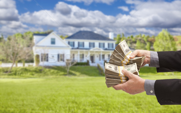 Man Handing Over Hundreds of Dollars in Front of House Stock photo © feverpitch