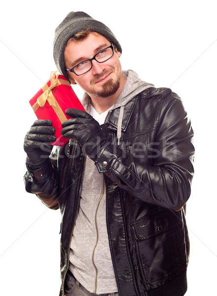 Warmly Dressed Young Man Holding Wrapped Gift To His Ear Stock photo © feverpitch