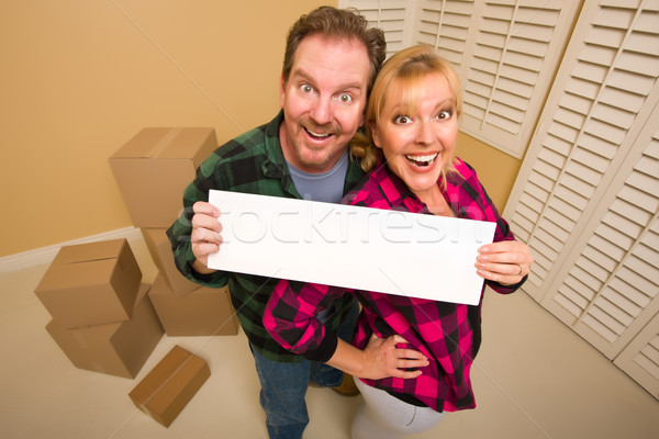 Happy Couple Holding Blank Sign in Room with Packed Boxes Stock photo © feverpitch