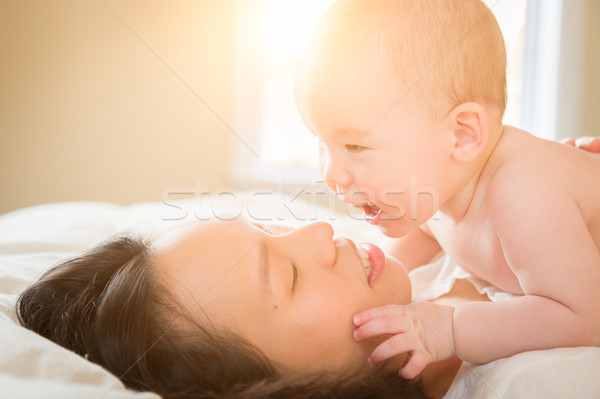 Mixed Race Chinese and Caucasian Baby Boy Laying In Bed with His Stock photo © feverpitch