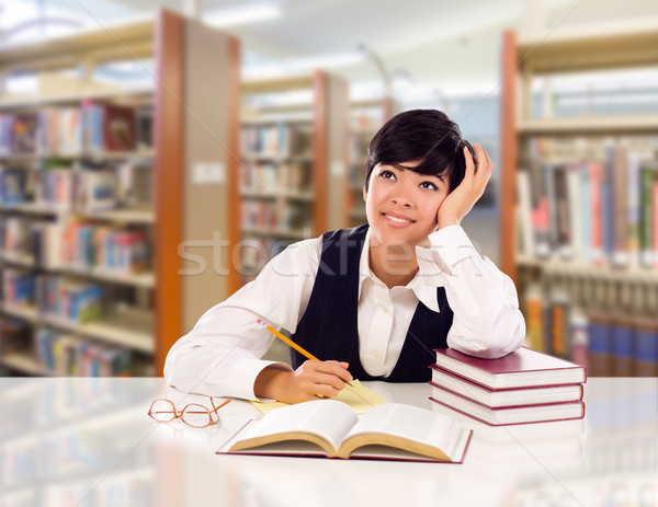 Young Female Mixed Race Student With Books and Paper Daydreaming Stock photo © feverpitch
