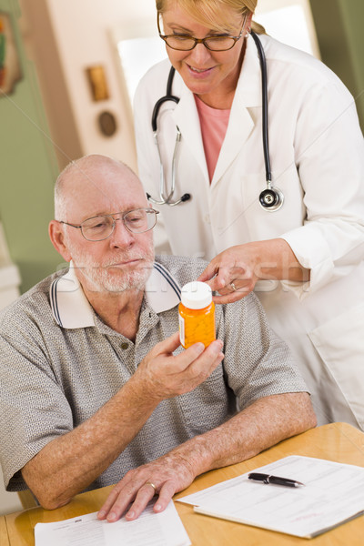 Doctor or Nurse Explaining Prescription Medicine to Senior Man Stock photo © feverpitch