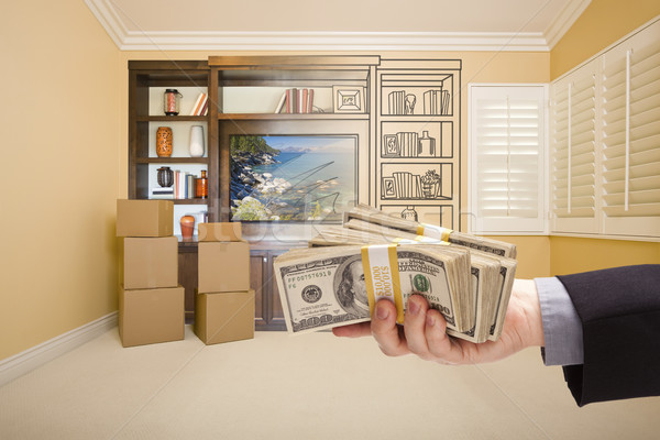 Holding Out Cash Over Drawing of Entertainment Unit In Room Stock photo © feverpitch