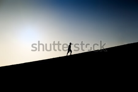 Silhouette of a man climbing a hill Stock photo © fisfra