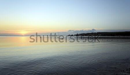 Sunrise plage vieux roches distance Photo stock © flotsom
