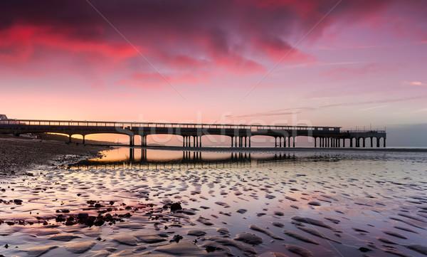 Pier plage faible marée coucher du soleil paysage Photo stock © flotsom