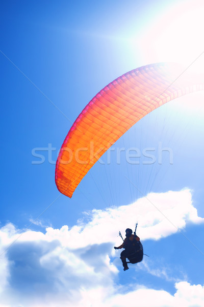 Paraglider silhouetted against a blue sky and clouds Stock photo © Forgiss